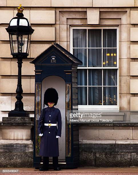 Queen´s guard outside Buckingham palace with his winter outfit He is inside the sentry box with a window that shows a chandelier lamp and a big...