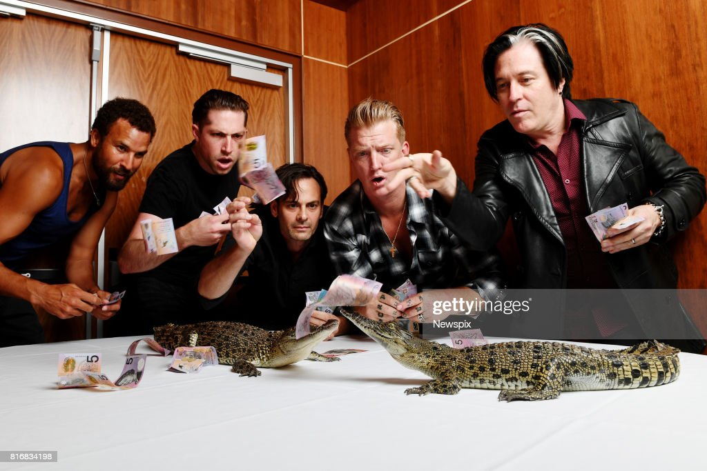 DARWIN, NT - (EUROPE AND AUSTRALASIA OUT) Queens of the Stone Age throw money at two crocodiles during a photo shoot in Darwin, Northern Territory.