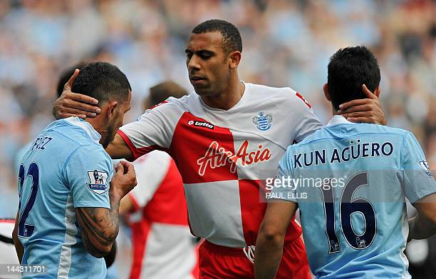 Queens Park Rangers' English defender Anton Ferdinand tries to calm Manchester City's Argentinian strikers Carlos Tevez and Sergio Aguero during the...