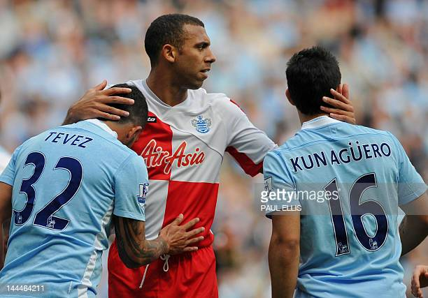 Queens Park Rangers' English defender Anton Ferdinand tries to calm Manchester City's Argentinian strikers Carlos Tevez and Sergio Aguero after an...
