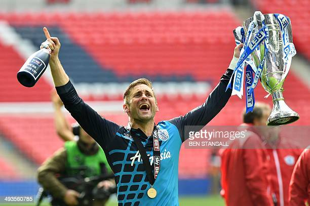 Queens Park Rangers' English goalkeeper Robert Green celebrates with the trophy after his team won the English Championship Play Off final football...