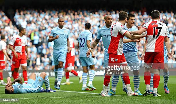 Queens Park Rangers' English midfielder Joey Barton clashes with Manchester City's Argentinian striker Sergio Aguero as Manchester City's Argentinian...