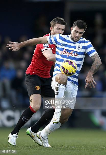 Queens Park Rangers' English striker Charlie Austin vies for the ball with Manchester United's English midfielder Michael Carrick during the English...