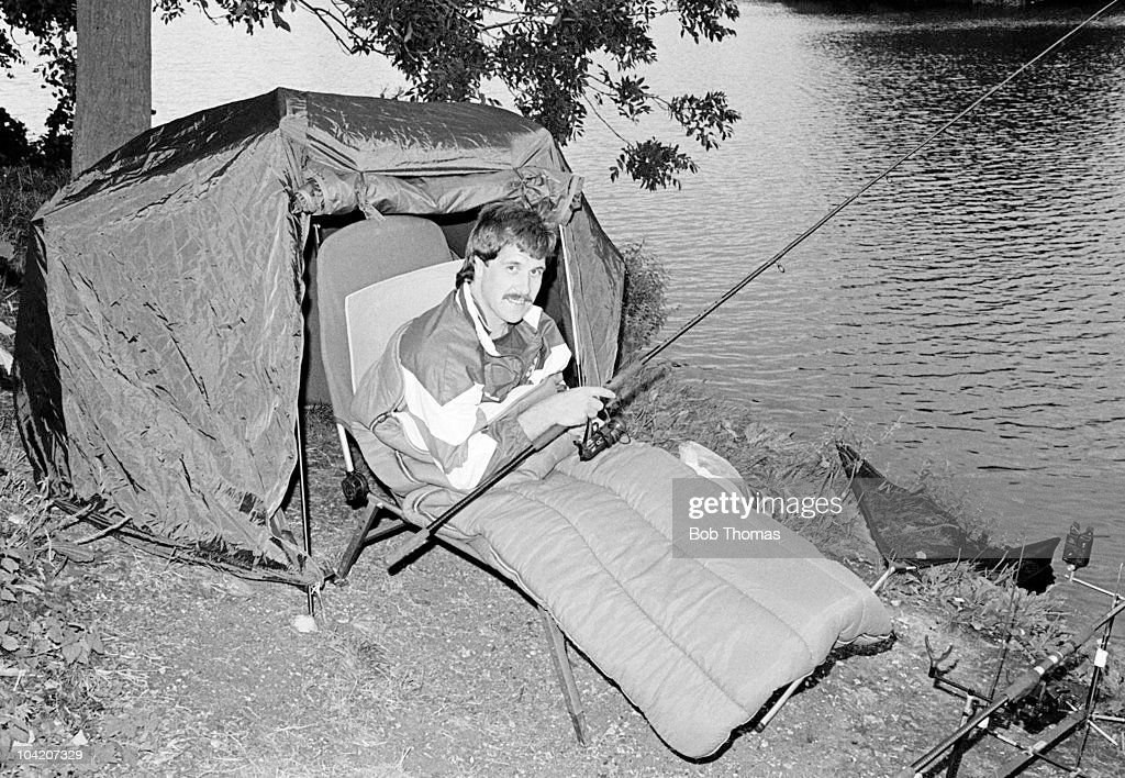 Queens Park Rangers goalkeeper David Seaman settles down for a night-fishing session at Farlows Lake, Iver, Buckinghamshire on 25th August 1988.