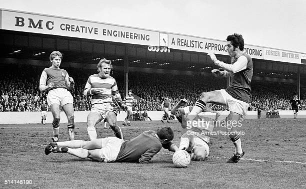 Queens Park Rangers goalkeeper Mike Kelly dives bravely at the feet of Aston Villa's Willie Anderson during their Second Division match at Villa Park...