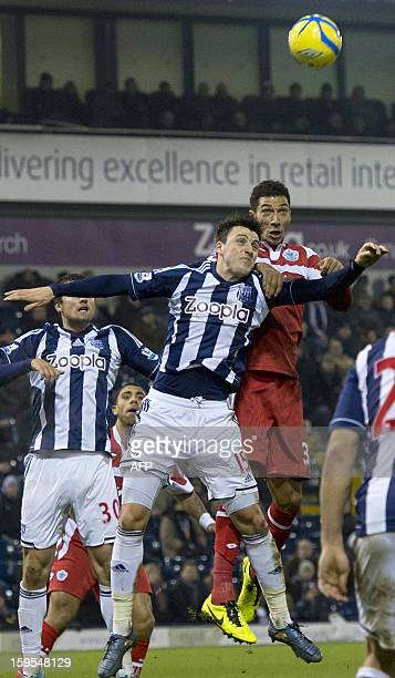 Queens Park Rangers' Jay Bothroyd jumps above West Bromwich Albion's English midfielder George Thorne to head the ball for a goal during the English...