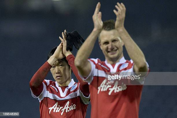 Queens Park Rangers' Korean midfielder Park JiSung and English defender Clint Hill gesture to the crowd following the English FA Cup third round...