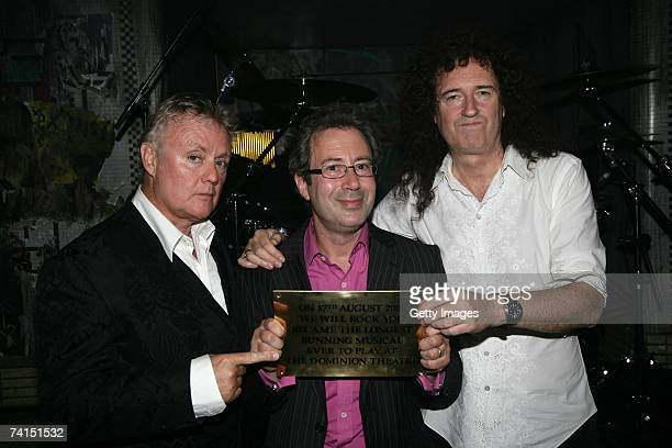 Queen's Roger Taylor and Brian May and writer Ben Elton pose backstage with a plaque to announce We Will Rock You as the longest running musical at...