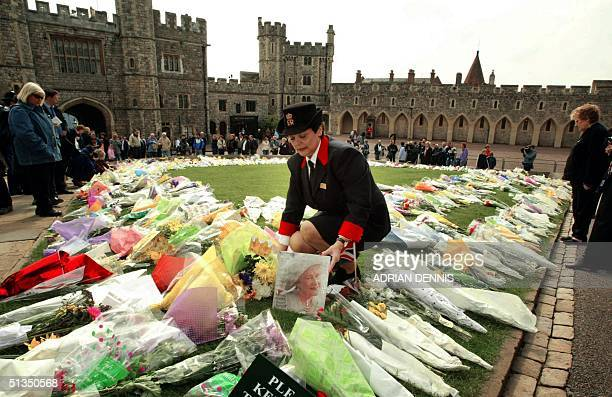 Queen's Warden adjusts a picture of The Queen Mother left amongst flowers outside St. George's Chapel 01 April 2002, in Windsor Castle. People have...
