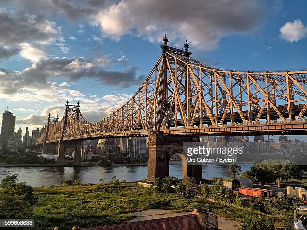 queensboro bridge over east river against cloudy sky - queens new york city - fotografias e filmes do acervo