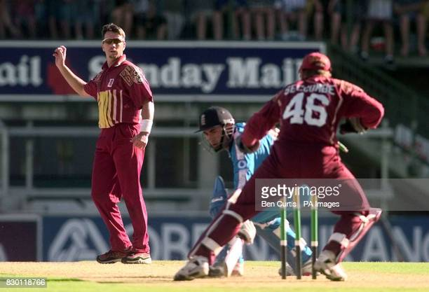 Queensland bowler Stuart Law throws the ball to keeper Wade Seccombe as England Captain Adam Hollioake narrowly avoids being runout during a match at...