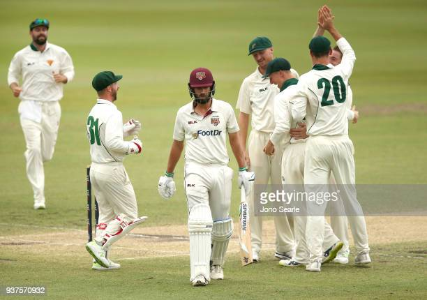 Queensland player Joe Burns leaves the ground after getting out as Tasmanian team mates celebrate during day three of the Sheffield Shield final...