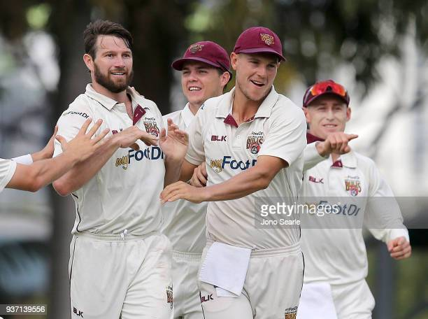 Queensland player Michael Neser celebrates taking a wicket with team mates Mitch Swepson and Charlie Hemphrey during day two of the Sheffield Shield...