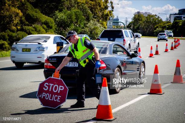 Queensland police officer moves a stop sign at a vehicle checkpoint on the Pacific Highway on the Queensland - New South Wales border, in Brisbane on...