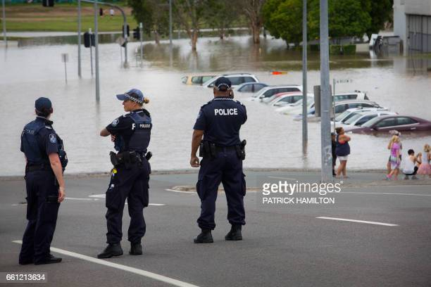 Queensland police officers stand watch over submerged cars at the flooded Beenleigh train station carpark on March 31 2017 Tens of thousands of...