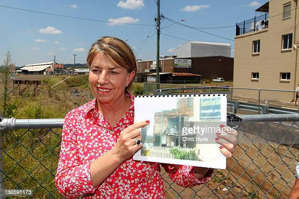 Queensland Premier Anna Bligh holds a photograph showing the damage of the floods on January 9 2012 in Toowoomba January marks one year since...