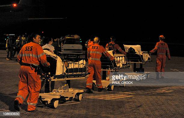 Queensland State Emergency Service volunteers wheel patients across the tarmac onto a Royal Australian Air Force C130 Hercules aircraft as hospitals...