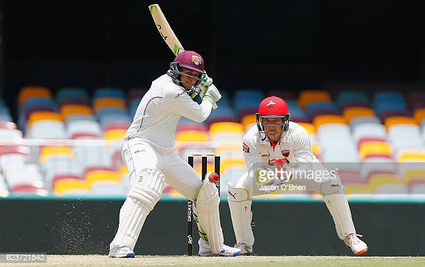 Queensland's Usman Khawaja plays a shot as Alex Carey looks on during day one of the Sheffield Shield match between Queensland and South Australia at...