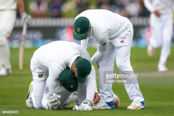 Quentin de Kock of South Africa is congratulated by Faf du Plessis and Dean Elgar after taking a catch to dismiss Neil Broom of New Zealand during...