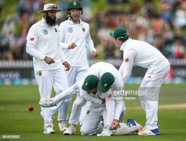 Quentin de Kock of South Africa is congratulated by teammates Faf du Plessis Hashim Amla Stephen Cook and Dean Elgar after taking a catch to dismiss...