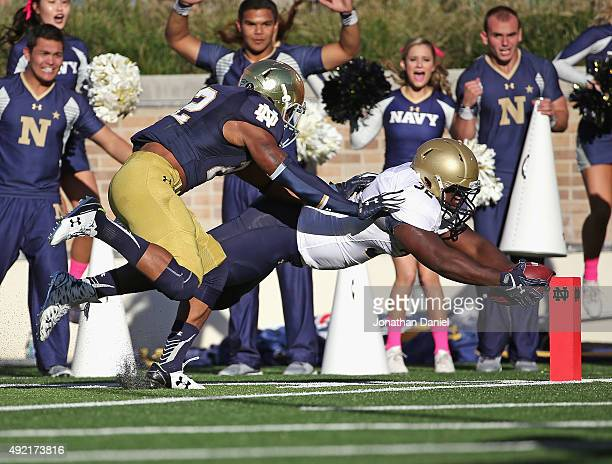 Quentin Ezell of the Navy Midshipmen dives into the end zone to score a touchdown as Elijah Shumate of the Notre Dame Fighting Irish tries to shove...