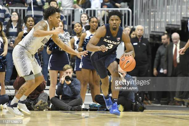 Quentin Goodin of the Xavier Musketeers dribbles by James Akinjo of the Georgetown Hoyas during a college basketball game at the Capital One Arena on...