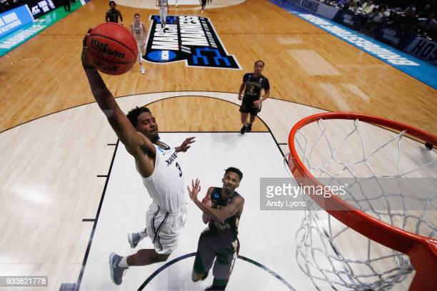 Quentin Goodin of the Xavier Musketeers dunks the ball over Braian Angola of the Florida State Seminoles during the second half in the second round...