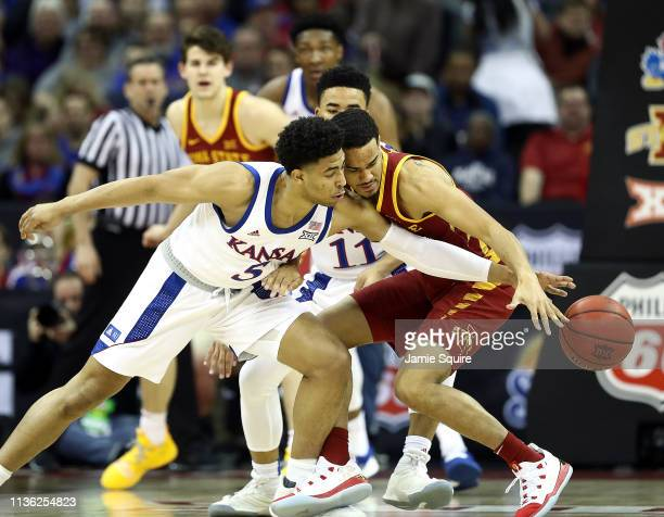 Quentin Grimes of the Kansas Jayhawks tries to steal the ball from Nick WeilerBabb of the Iowa State Cyclones during the Big 12 Basketball Tournament...