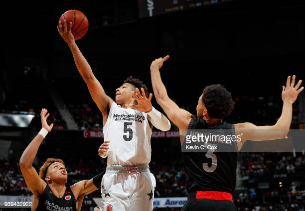 Quentin Grimes of The Woodlands College Park HS attacks the basket against Romeo Langford of New Albany High School and EJ Montgomery of Wheeler High...