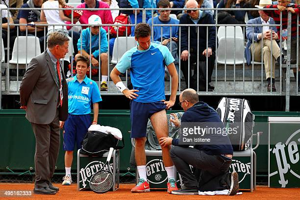 Quentin Halys of France receives assistance from the trainer during a medical timeout in his boys' singles match against Nicolae Frunza of Romania on...