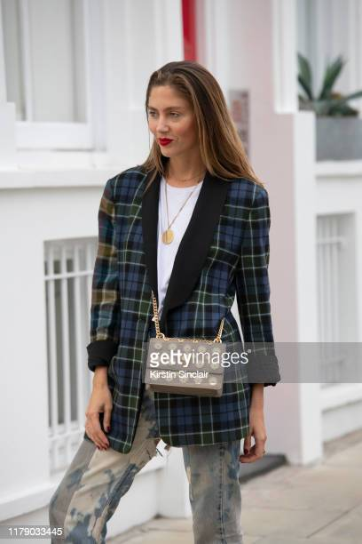 Quentin Jones wears a Tibi checked blazer white Tshirt Elm stone washed jeans and a Kurt Geiger bag on October 04 2019 in London England