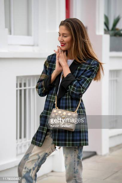 Quentin Jones wears a Tibi checked blazer, white T-shirt, Elm stone washed jeans and a Kurt Geiger bag on October 04, 2019 in London, England.