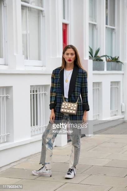 Quentin Jones wears J.W Anderson for Converse trainers, a checked blazer, white T-shirt, stone washed jeans and a Kurt Geiger bag on October 04, 2019...