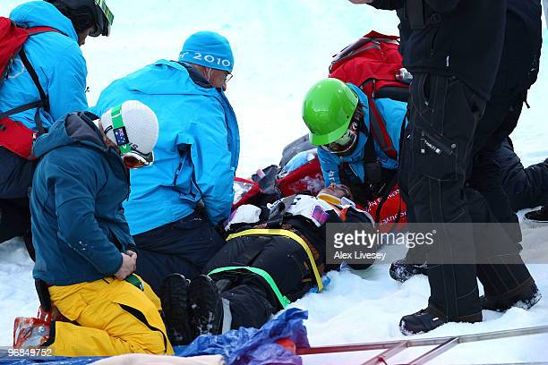 Queralt Castellet of Spain is tended to as she lies in the snow after she was injured during a practice run for the women's snowboard halfpipe on day...