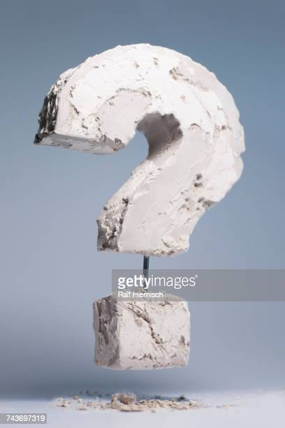 Question mark made of stone material levitating against gray background