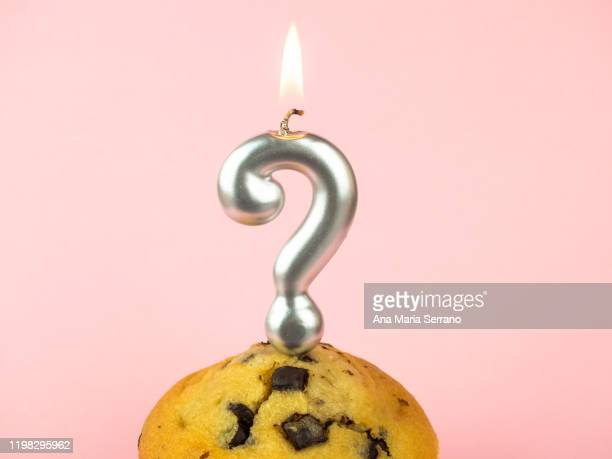 question marks birthday candles on a cupcake with chocolate pieces on a pink background - q and a stock pictures, royalty-free photos & images