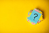 question marks written reminders tickets on yellow vintage paper background