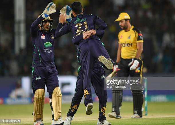 Quetta Gladiators Pakistani captain Sarfraz Ahmed celebrates with his teammates after dismissing Peshawar Zalmi cricketer Sohaib Maqsood during the...