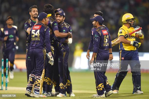 Quetta Gladiators players celebrate the dismissal of batsman Kamran Akmal of Peshawar Zalmi during the PSL T20 cricket match in the Gaddafi Stadium...