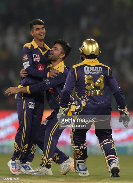 Quetta Gladiators spinner Hassan Khan celebrates with teammate Ahmed Shehzad and team captain and wicketkeeper Sarfraz Ahmed after taking the wicket...