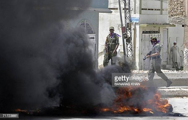 Pakistani antiterror force personals walk past burning tyres after they were set on fire by angry protesters in Quetta 27 August 2006 over the...
