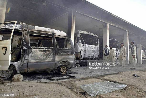 Pakistani men look at a burning bus stand after it was set on fire by angry protesters in Quetta 27 August 2006 against the killing of tribal rebel...