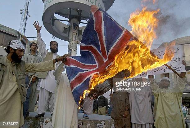 Pakistani Muslim men shout slogans in front of a burning British flag during a protest rally in Quetta 24 June 2007 Pakistan's Prime Minister joined...