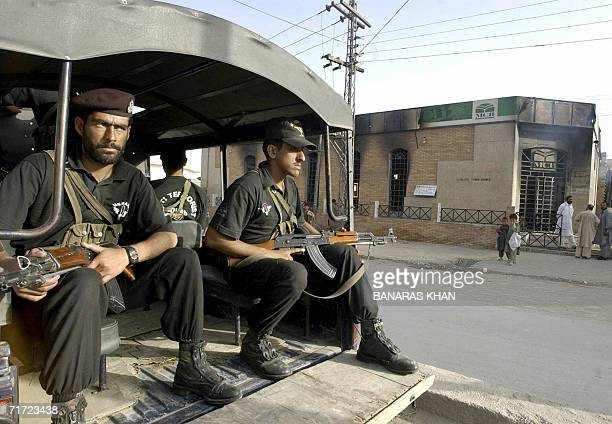 Pakistani police commandos guard in front of a bank after it was set on fire by angry protesters in Quetta 27 August 2006 against the killing of...
