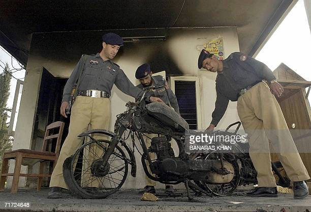 Pakistani policemen examine a burnt motorcycle after it was set on fire by protesters in Quetta 27 August 2006during a protest against the killing of...