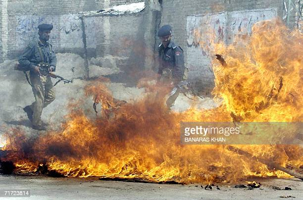 Pakistani policemen stand behind burning tyres after they were set on fire by angry protesters in Quetta 27 August 2006 over the killing of tribal...