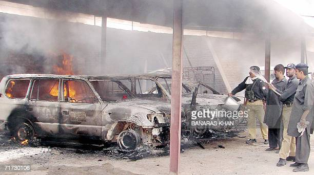 Pakistani policemen try to extinguish burning vehicles set on fire by an angry mob during a protest against the killing of tribal chief Nawab Akbar...