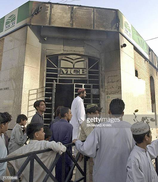 Pakistani residents gather in front of a bank after it was set on fire by angry protesters in Quetta 27 August 2006 against the killing of tribal...