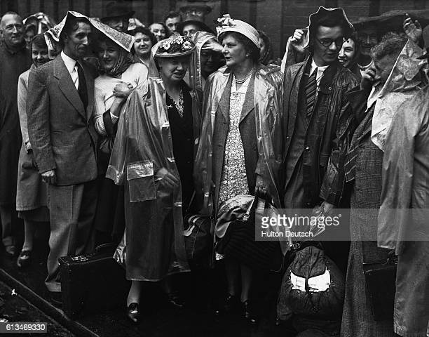 A queue at Waterloo Station is caught in the rain as a record number of holiday crowds converge there Shown are Mr and Mrs Atkinson Mrs Leoni Sof Mrs...
