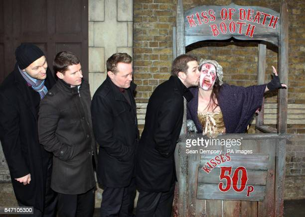 A queue forms behind Kevin Haney from London as he kisses Pretty Polly the Plague Victim in the London Dungeon Kiss of Death booth which has opened...